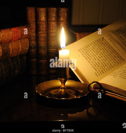 Antiquarische Bücher mit Kerzenlicht beleuchtet Stockbild