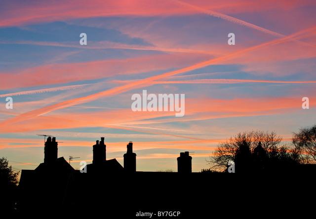 Flugzeug-Kondensstreifen durch die Einstellung Sonne und roten Himmel über diese Cheshire Schornstein Tops Stockbild
