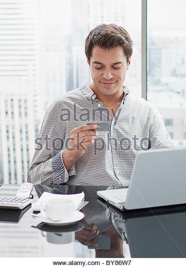 Geschäftsmann mit Kreditkarte zum Einkaufen im internet Stockbild