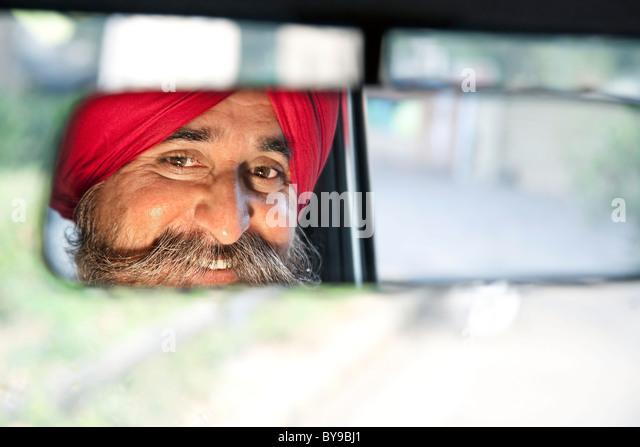 Sikh Taxifahrer Blick in den Rückspiegel Stockbild