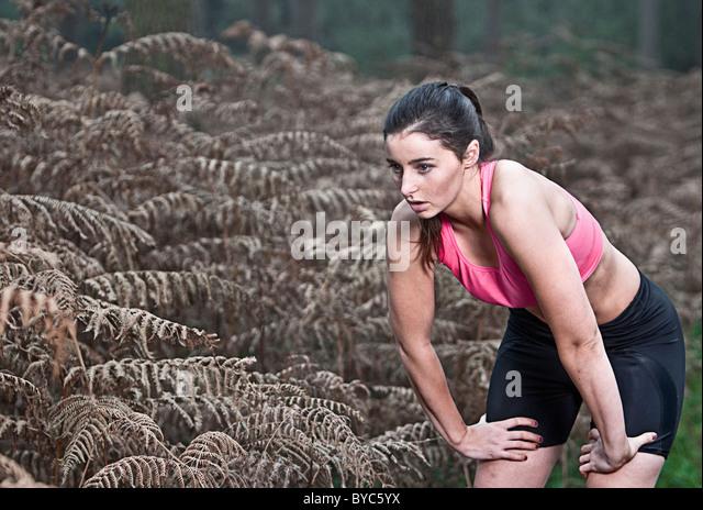 Weibliche Verschnaufpause vom Lauf im Wald Stockbild