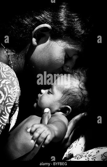 Junge Süd indische Mutter wiegt ihr neugeborenes Baby. Schwarz / weiß Stockbild