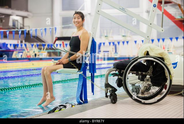 eine Querschnittsgelähmte Frau betritt einen Swimming Pool auf einer Hebebühne mit ihrem Rollstuhl am Stockbild
