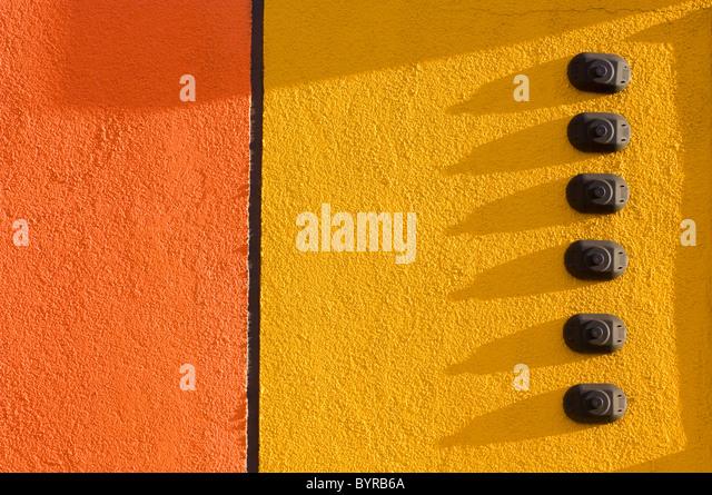 Orange und gelbe Stuck Wand mit 6 Türklingeln; St. Albert, Alberta, Kanada Stockbild