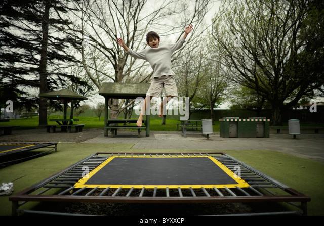 Junge springt auf Trampolin im öffentlichen Spielplatz, Neuseeland. Stockbild