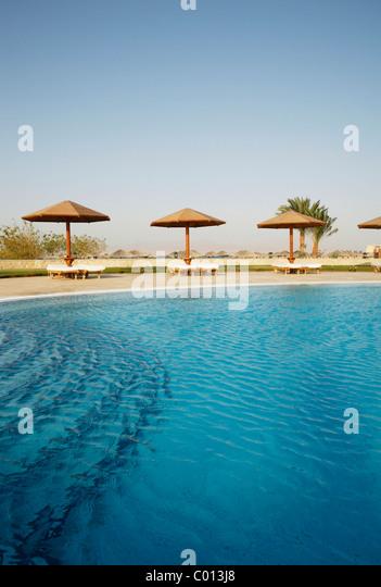 Pool mit einer blauen Wasseroberfläche, Sonnenliegen und Sonnenschirme, Soma Bay, Rotes Meer, Ägypten, Stockbild