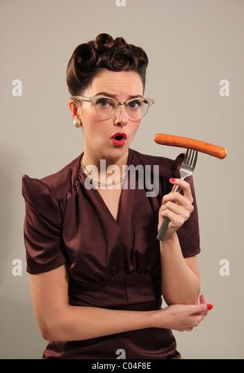 Retro-Frau hält eine Wurst Stockbild
