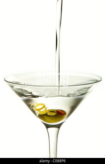 Ein Glas Martini Cocktail mit Olive Garnish und gießen Sie auf einem weißen Hintergrund. Stockbild
