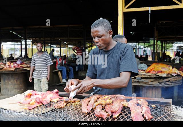 Mann, Grillen von Fleisch auf einem Markt in der Township Katutura, Windhoek, Namibia, Afrika Stockbild