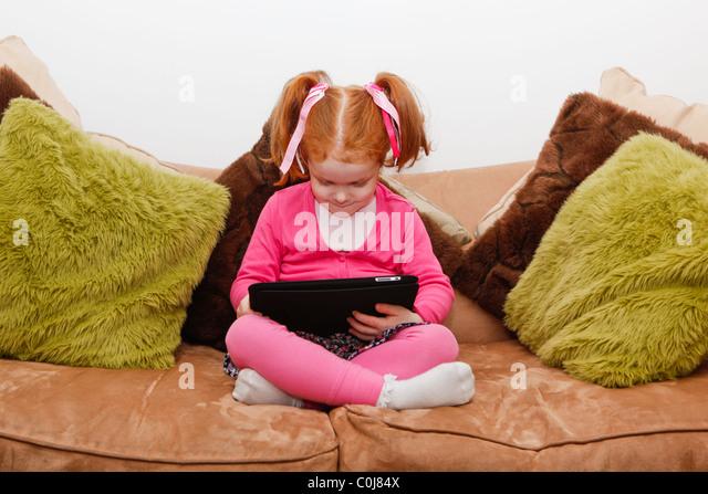Kleines Mädchen mit roten Haaren spielen auf dem Ipad, Tablet Computer, auf dem Sofa sitzend. Stockbild