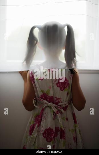 Mädchen schaut aus dem Fenster hinter der Gardine - Stock-Bilder