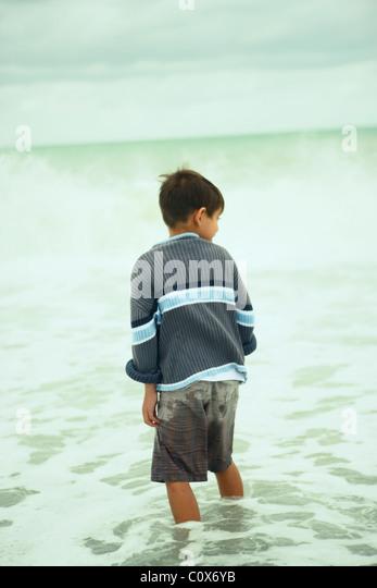 Acht Jahre alter Junge im Meer an einem bewölkten herbstlichen Tag, Napier, Neuseeland Stockbild