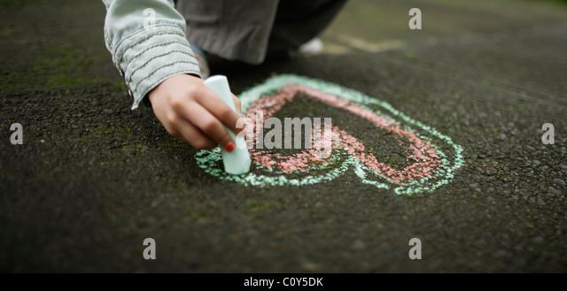 Mädchen Zeichnung Kreide Herz am Boden Stockbild