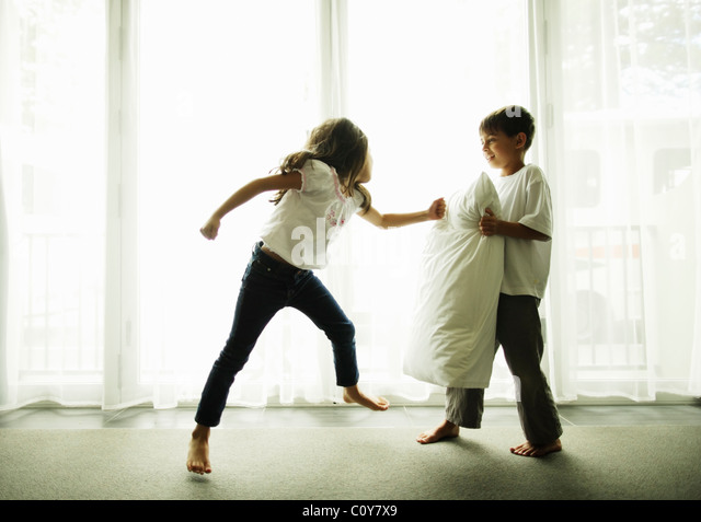 Junge hält Kissen als Boxsack für seine Kung-Fu-Schwester. Stockbild