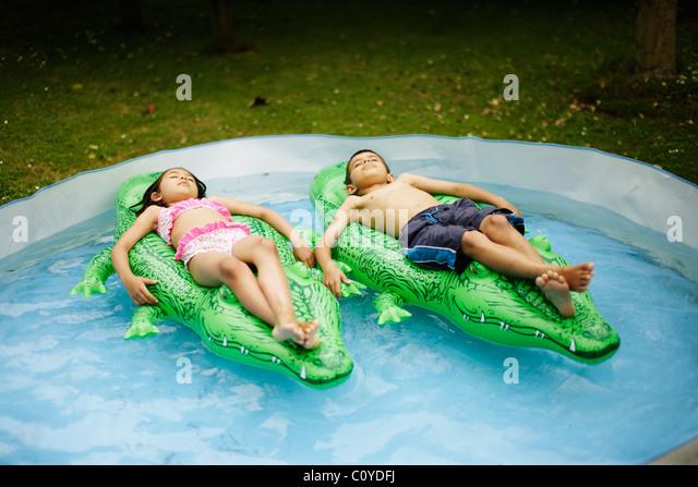 Jungen und Mädchen liegen auf aufblasbaren Krokodilen im Planschbecken schweben. Stockbild