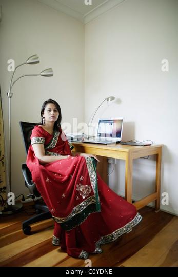 Home-Office. Punjabi Frau im roten Sari Heimarbeit mit Schreibtisch im Wohnzimmer. Stockbild