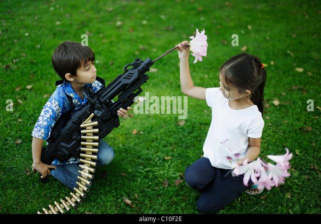 Fünf Jahre altes Mädchen legt Blumen im Lauf ihres Bruders Spielzeug Maschine Pistole Stockbild