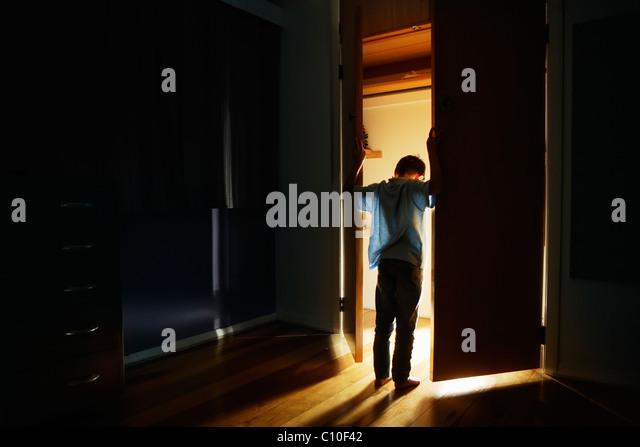 Junge steht bei Schranktüren innerhalb von beleuchtet Stockbild