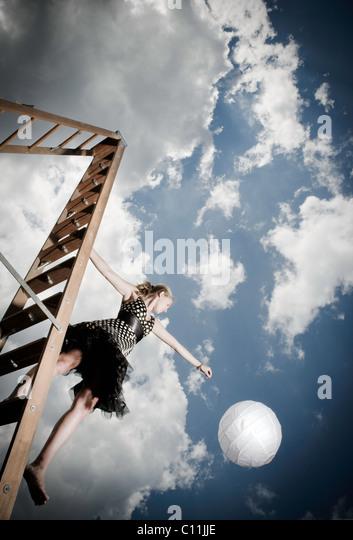 Ein junges Mädchen tragen eine schwarzen und weiße Polka punktierte Kleid steht auf einer Leiter halten Stockbild