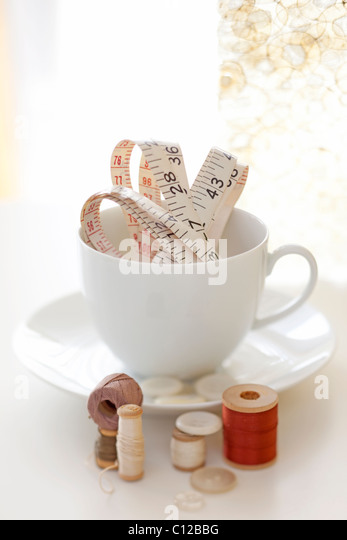 Tee Tasse halten Messen Band und Faden und Nähen Artikel Stockbild