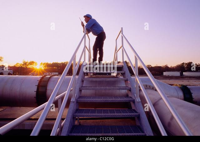 Ingenieur auf ein Walkie Talkie Funkgerät bei Sonnenuntergang auf einer Kläranlage, Houston, Texas, USA Stockbild