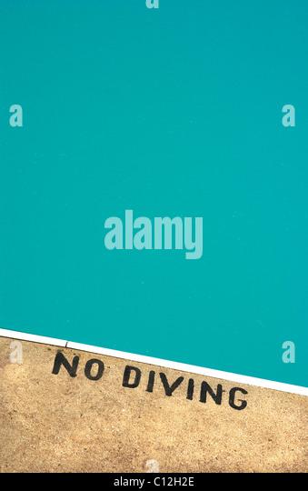 Ein Schwimmbad mit einem keine Tauchen Schild gemalt auf den Rand des Pools. Stockbild