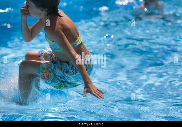 junges Mädchen ins Schwimmbad springen Stockbild
