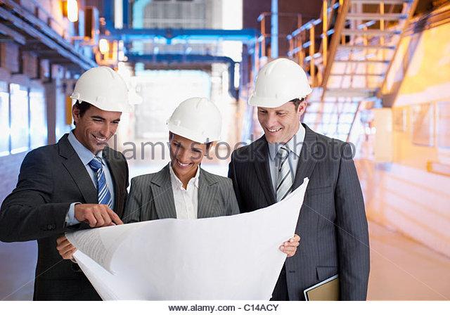 Geschäftsleute, die Überprüfung der Entwürfe in Fabrik - Stock-Bilder