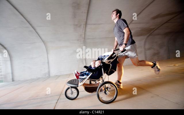 Ein Mann läuft durch einen Tunnel mit seinen zwei Söhnen in einem Kinderwagen. (Motion Blur) Stockbild