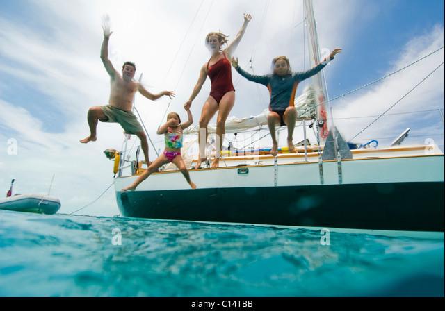 Eine Familie von ihrem Boot zu springen Stockbild