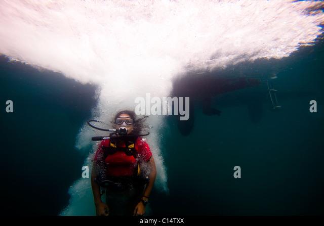 Eine junge Hispanic Frau in Tauchausrüstung springt in den Ozean. Stockbild