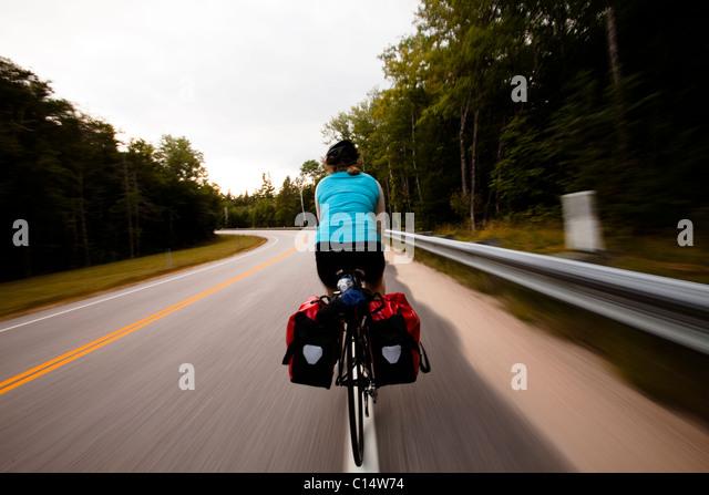 Ein weibliche Radfahrer klettert auf dem Kancamagus Highway.  Bewegungsunschärfe. Stockbild