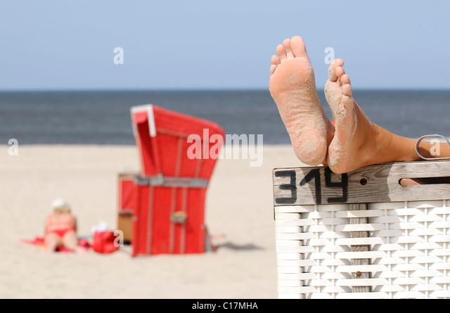 Füße auf einer überdachten Strandkorb in der Nähe von Wenningstedt, Sylt, Nord-friesische Insel, Stockbild