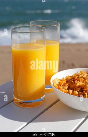 Gläser Orangensaft und eine Schüssel Müsli am Meer. Stockbild