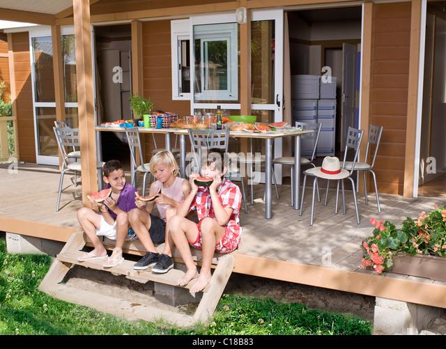 Jungen Essen Wassermelone Sit auf wenige Schritte vor Stockbild