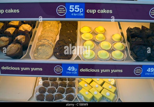 Auswahl an ungesunden Kuchen auf dem Display im schottischen High Street-Bäckerei-Fenster Stockbild