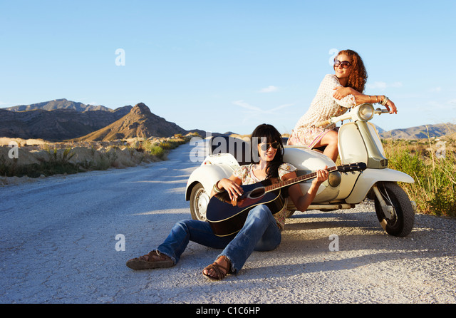 Frauen, die Ruhe auf der Straße mit Motorrad Stockbild