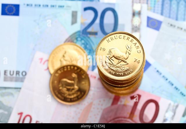Ein Stapel von Krügerrand auf Euro-Banknoten Stockbild