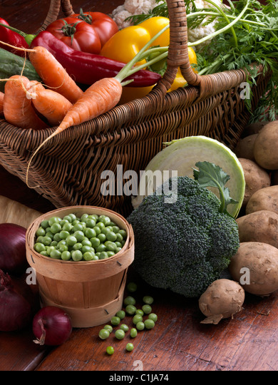 Wicker Korb rohes Gemüse Tomaten süß rot gelb Paprika Karotten Erbsen Blumenkohl Pastinaken Brokkoli Stockbild