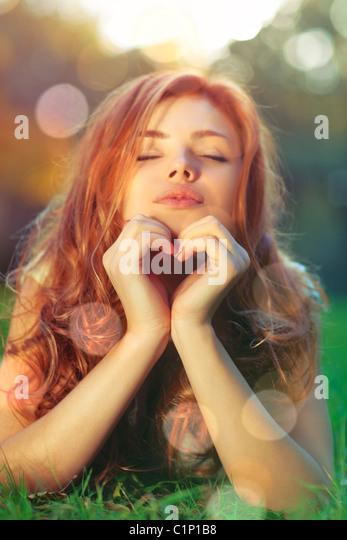 Junge Frau auf dem Rasen liegen und zeigen Herz-Form-Porträt. Stockbild
