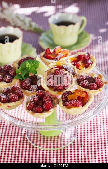 Kuchen mit Himbeeren auf Gartentisch Stockbild