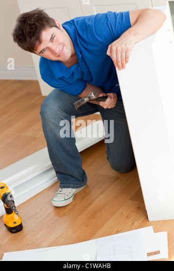 Lächelnd Mann Montage von Möbeln und halten einen hammer Stockbild