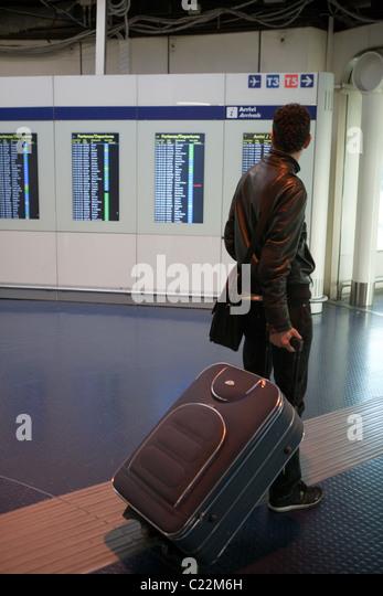 Person, die über den Status Tabelle Abflüge Ankünfte Flughafen innen Rom Fiumicino Italien Stockbild