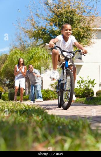 Eine junge afroamerikanische Familie mit jungen Kind reiten sein Fahrrad und seine glücklichen begeisterten Stockbild
