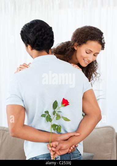 Schöne Frau zu finden, eine Rose von seinem Freund versteckt Stockbild