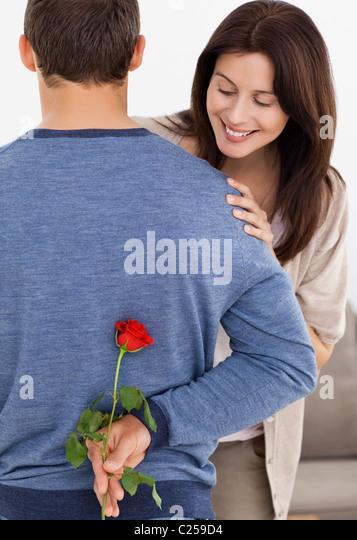 Impatiente Frau betrachten einer Blume versteckt von ihrem Freund Stockbild