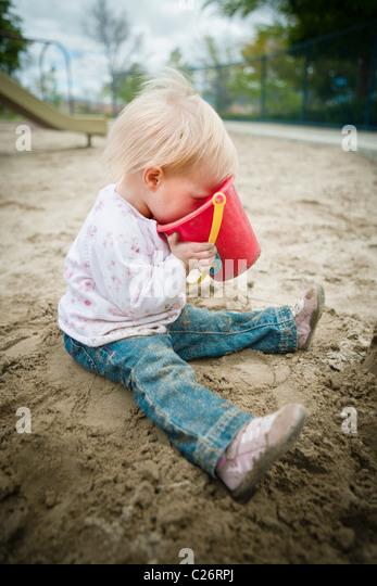 1 Jahre altes Mädchen in Spielplatz Sandkasten mit Sand Spielzeug spielen Stockbild