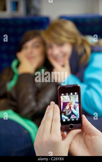 Mädchen mit dem Fotografieren von Freunden mit einem Smartphone Stockbild