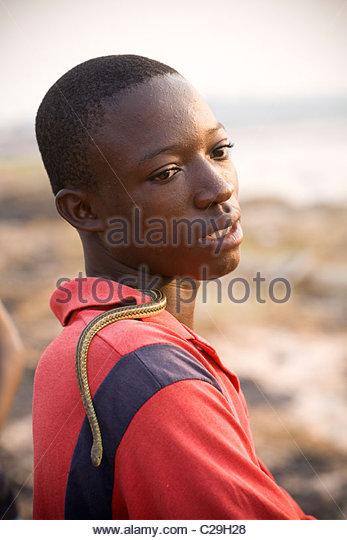 Ein junger kongolesischer Mann mit einer Schlange entlang des Kongo-Flusses. Stockbild