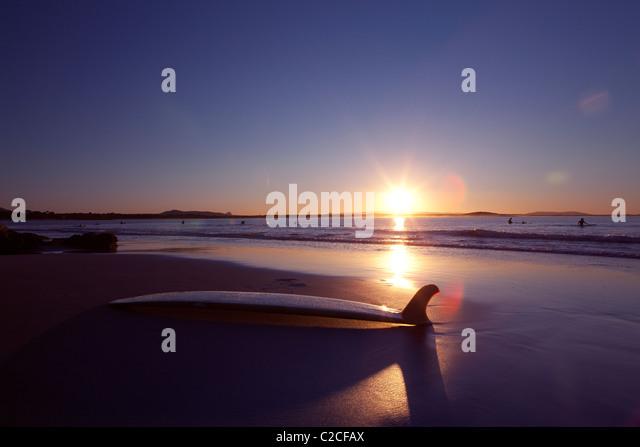 Surfbrett am Strand bei Sonnenuntergang Stockbild
